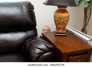 Caucasian Toddler Infant Baby Boy Hides Behind Furniture Peeking