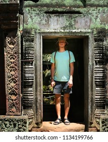 Caucasian tourist inside ancient ruin. Young tall adult men explores south asian culture. Old ruins of temple in Cambodia. Tourism and travel concepts.
