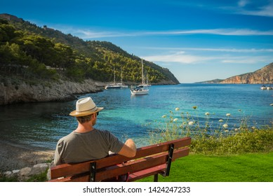 Caucasian tourist with a straw hat sitting on a bench admiring the view to the bay of Assos in Greece with sailing boats in the background on a sunny day - with fake grass