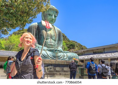 Caucasian tourist woman taking selfie stick picture photo with a smartphone at Great Buddha in Kotoku-in Buddhist Temple, Kamakura. Young happy traveler in Japan. Beautiful springtime in the blue sky.