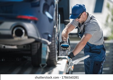 Caucasian Towing Company Worker inn His 40s Securing Modern Vehicle on the Towing Truck Platform. Cars Transportation Business.
