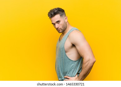 Caucasian trainer man posing against a yellow background