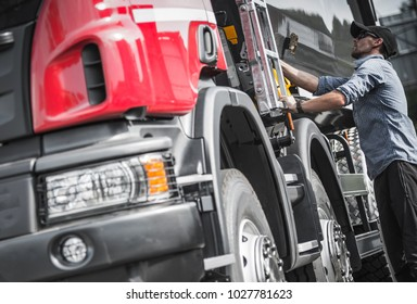 Caucasian Truck Driver Final Load Check Before Hitting the Road. Heavy Duty Transportation Theme.