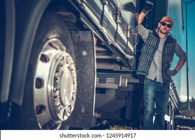 Caucasian Truck Driver in His 30s Between Semi Trailers. Transportation and Logistics Theme.