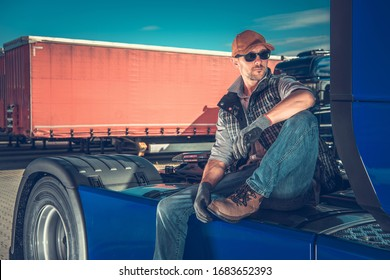 Caucasian Truck Driver in His 30s Chilling Out on the Back of His Semi Tractor. Relaxing on the Truck Stop. Transportation Industry Theme.