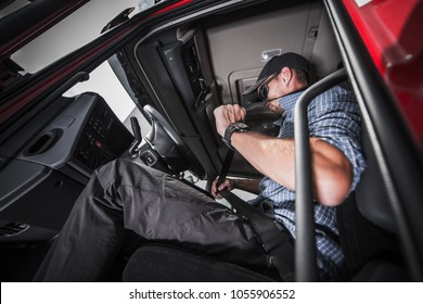 Caucasian Truck Driver Using Seat Belts For his Safety. Heavy transportation Safety.