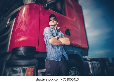 Caucasian Trucker in His 30s and His Red Euro Semi Truck Tractor. Transportation and Shipping Industry.
