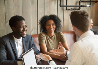 Caucasian wedding planner consulting black couple on marriage ideas in coffee shop, broker or realtor talking to African American clients, considering property offers in casual atmosphere in cafe