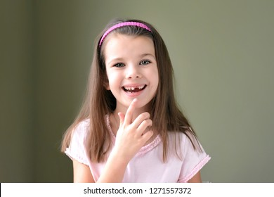 Caucasian white beautiful long haired brunette toothless girl with pink hair band. Smiling cute kid without front milk tooth. Kid expression portrait with fun happy face, who lost his first tooth.