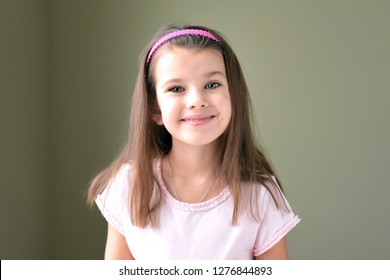 Caucasian white beautiful long haired brunette smiling toothless girl with pink hair band. Smiling cute kid without front milk tooth. Kid expression portrait with fun happy face, who lost his tooth