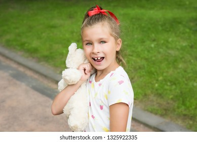 Caucasian white beautiful long haired brunette smiling toothless girl with red hair band. Smiling cute kid without front milk tooth. Kid expression portrait with fun happy face, who lost his tooth