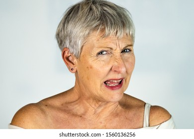 caucasian White haired older woman with furious look and screaming in White background