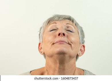 caucasian White haired older woman with her head back isolated on White background, expression of happiness