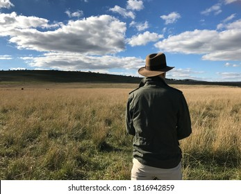 Caucasian, white, male in vintage travel outfit. Wearing light brown fedora, green safari jacket with white pants. Person is in field with blue sky background with clouds. Feeling of adventure travel