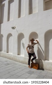 Caucasian, white, male in vintage travel outfit. Wearing light brown fedora, linen shirt and carrying vintage suitcase. Feeling of adventure travel and nostalgia. Arabic, Middle Eastern background.