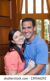 Caucasian wife and hispanic husband standing in entryway of home with tall wooden door, and windows, high ceilings, smiling during day.