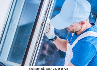 Caucasian Windows Technician Making Sure the Window is Installed Correctly.