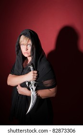Caucasian witch wearing in hood with athame dagger