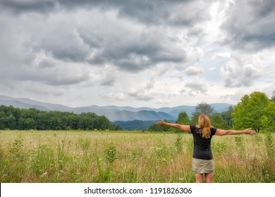 Caucasian woman with arms outstretched soaking in the Great Smoky Mountains in a Meadow in Cades Cove
