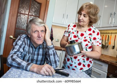 Caucasian woman asks her husband for help with housework, man covers his ear with his hand