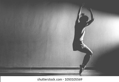 Caucasian woman ballet dancer, in black and white clothes dancing in a studio, she has her arms up and is is on her tippy toes with her knees bent in a dark space with a bright light shining on her