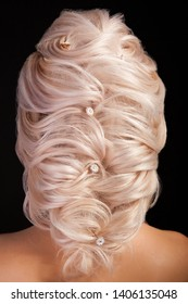 Caucasian woman with beautiful long blonde hair and glamour coiffure on studio background. Close up shot of hair style.