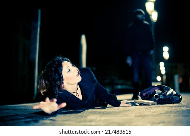 Caucasian woman being assaulted by a man in a dark alley.  Aggression concept.