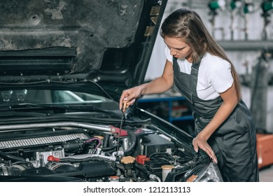 Caucasian woman in a black jumpsuit and a white t-shirt checking the oil level in a black car in the garage.
