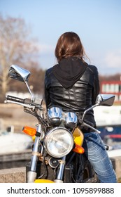 Caucasian woman in black leather jacket turn back upon while sitting on motorcycle