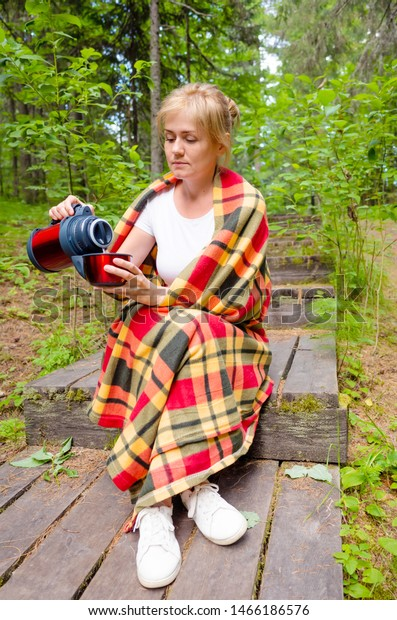 Caucasian woman blonde sits on a wooden path and pours tea from a thermos into a cup. Around her trees, plants. The concept of comfort, unity with the northern nature, Hygge, Lagom.