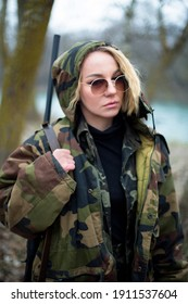caucasian woman in camouflage suit and sunglasses with shotgun on the shoulder near the river