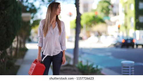 Caucasian woman carrying plastic jerrycan in need of fuel alone on city sidewalk