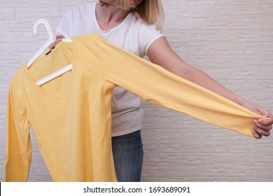 Caucasian woman choosing clothes, she is holding a hanger with yellow longsleeve , shopping, fitting and buying clothes during sale and discount concept, cheap second hand clothes for online selling.