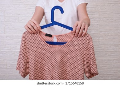 Caucasian woman choosing clothes, she is holding a hanger with beige t-shirt , shopping, fitting and buying clothes during sale and discount concept, cheap second hand clothes for online selling.