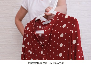 Caucasian woman choosing clothes, she is holding a hanger with fashionable shirt, shopping, fitting and buying clothes during sale and discount concept, cheap second hand clothes for online selling.