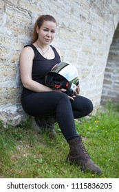 Caucasian woman with crash helmet in hands and protective boots sitting on green grass