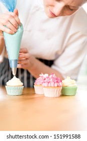 Caucasian woman decorating delicious homemade cupcakes with cream