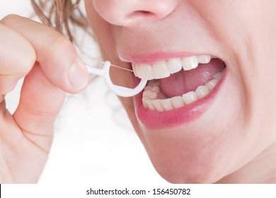 Caucasian woman with dental floss stick.