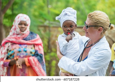 Caucasian woman doctor holding black little girl , African black woman in the background
