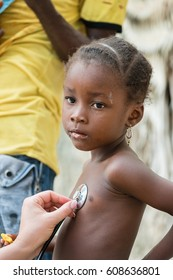 Caucasian woman doctor listening the hearth beat and breathing of African black little girl with stethoscope.Unrecognizable doctor