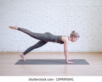 Caucasian woman doing plank on mat in pilates studio. Yoga, fitness, wellness, balance and smart body concept.