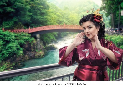 Caucasian woman dressed in Japanese traditional kimono poses against traditional Japanese arched bridge over the river in Nikko town.