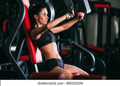 caucasian woman exercising on shoulder press machine