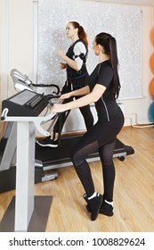 Caucasian woman exercising on treadmill in gym. Female trainer manages electric muscle stimulation purposed to increase effectiveness of training. Vertical shot
