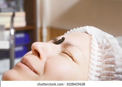 Caucasian woman face fearful of medicinal leech laying down on her forehead. Hirudotherapy helps to gain better blood flow and circulation. Closeup horizontal shot