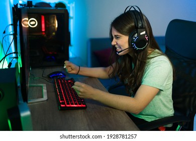 Caucasian woman feeling happy and excited while doing a winning gesture because of her victory in an online video game at her gaming computer PC