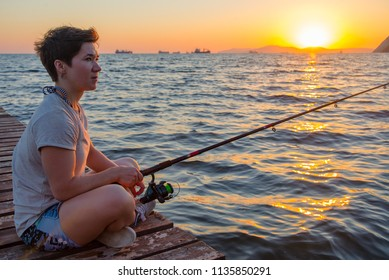 Caucasian woman is fishing with a fishing rod. a saturated sea sunset