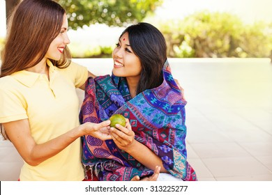 caucasian woman giving food to poor indian woman