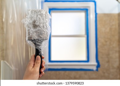 Caucasian woman hand holds up a paintbrush wrapped in plastic wrap to protect the brush from drying out while waiting to paint another coat