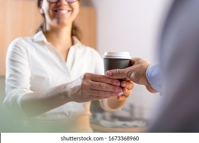 Caucasian woman hands a coffee cup to a man in a coffee shop